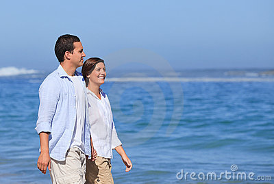 Couple walking on the beach under the sun