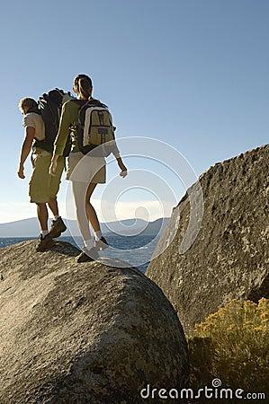 Couple Walking On Boulder At Coast