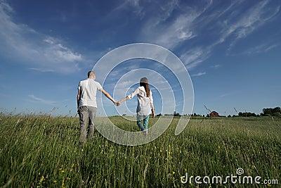 Couple walking through green field