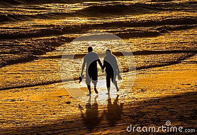 Couple walking holding hands beach