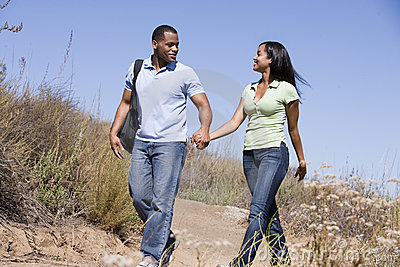 Couple walking on path holding hands and smiling
