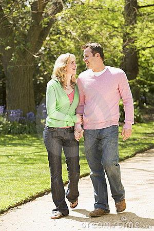 Couple walking on path holding hands smiling
