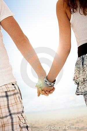 Couple walking on summer beach hand in hand