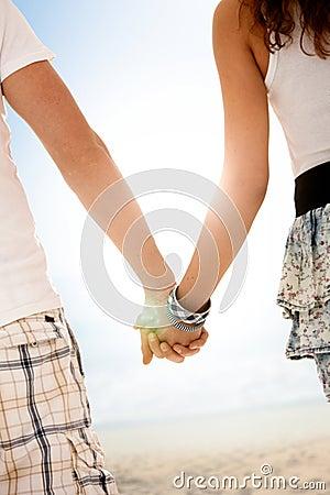 Couple walking on summer beach hand in hand