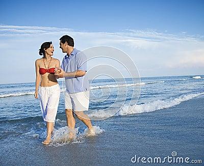 Couple walking in waves.