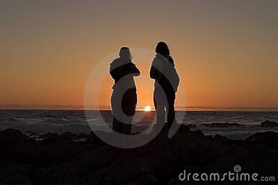 Couple watching ocean sunset