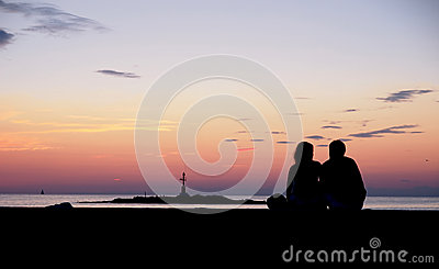 Couple watching the sunset by the sea