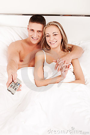 Couple watching TV in bedroom