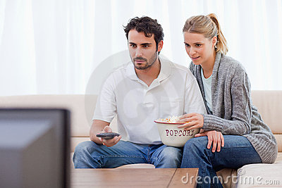 Couple watching TV while eating popcorn