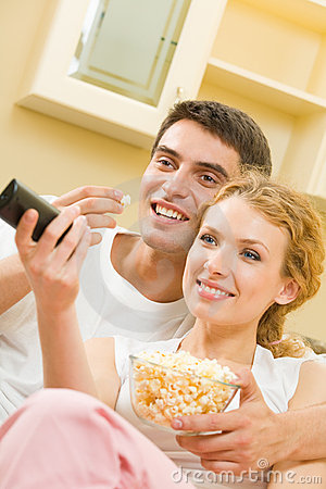 Couple watching TV with popcorn