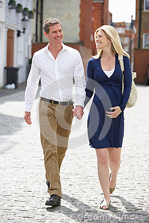 Free Couple With Pregnant Wife Walking Along Urban Sidewalk Stock Photos - 33700073