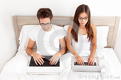 Couple working on laptops in bed