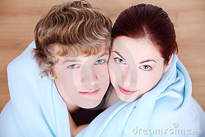 Couple wrapped in blanket.