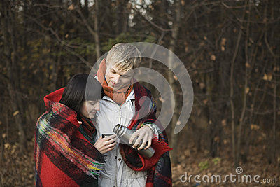 Couple Wrapped In Blanket Having Hot Tea
