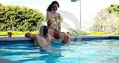 Couples agissant l'un sur l'autre les uns avec les autres au poolside banque de vidéos