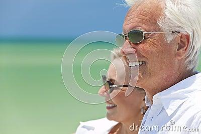 Couples aînés heureux par la mer sur une plage tropicale