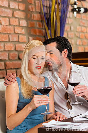 Couples attrayants buvant du vin rouge dans le restaurant