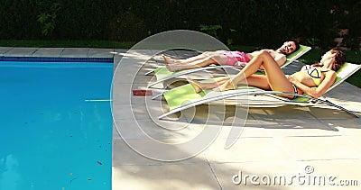 Couples détendant sur la chaise longue au poolside banque de vidéos