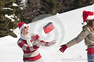Couples de Noël jouant avec des cadeaux dans la neige