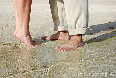 Couples feet standing on beach
