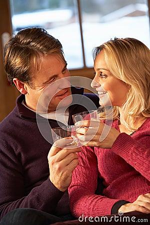 Couples âgés moyens sur le sofa avec le whiskey