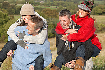 Couples Having Piggyback Ride In Autumn Landscape