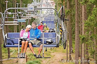 Couples insouciants voyageant par le bois d ascenseur de chaise