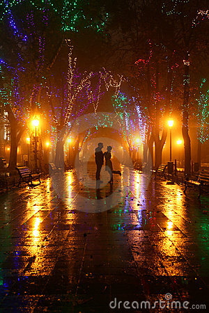 Couples marchant à la ruelle dans des lumières de nuit