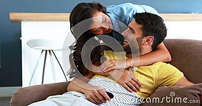 Couples parlant tout en regardant la télévision dans le salon banque de vidéos