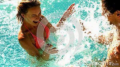Couples sexy éclaboussant dans la piscine ensemble en vacances clips vidéos