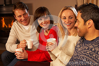 Couples Sitting On Sofa With Hot Drinks Talking