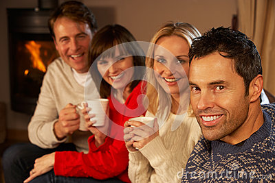 Couples Sitting On Sofa With Hot Drinks Talking Stock Images - Image: 25642184