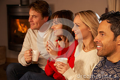 Couples Sitting On Sofa With Hot Drinks Wathing TV