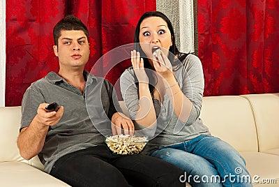 Couples stupéfaits regardant la TV