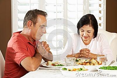 Couples supérieurs indiquant la grâce avant repas à la maison