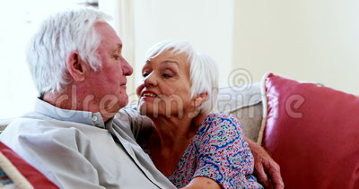 Couples supérieurs parlant tout en regardant la télévision dans le salon banque de vidéos