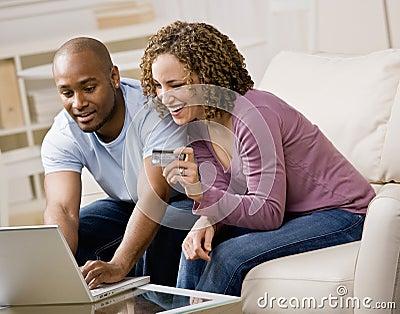 Couples utilisant par la carte de crédit à faire des emplettes en ligne