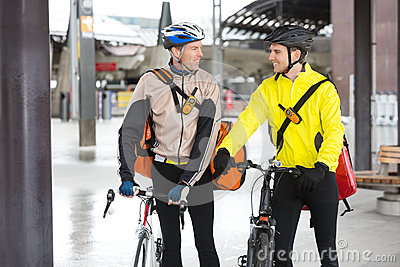 Courier Delivery Men With Bicycles Looking At Each