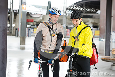 Courier Delivery Men With Bicycles Using Digital