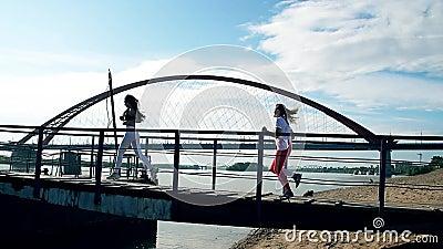 Course de filles plus de le pont sur la plage sablonneuse Les cheveux flottant, le soleil brillent, ciel bleu banque de vidéos