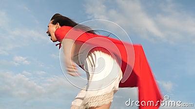 Course et rire dr?les de fille de super h?ros dans le manteau rouge, manteau flottant dans le vent La jeune femme gaie joue dans  banque de vidéos