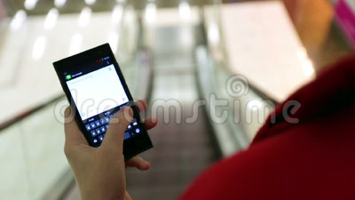 Court en gros plan de la femme dactylographiant sur un dispositif de smartphone tout en passant l'escalator banque de vidéos