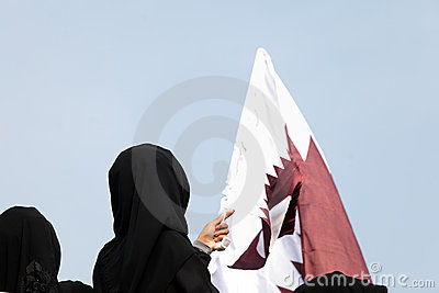 Covered women and Qatar flag