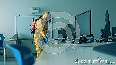Covid19, koncepcja koronawirusa Pracownik w hazmat oczyszcza biurka z komputerami zdjęcie wideo