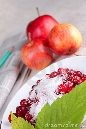 Cowberry, red apples and newspaper