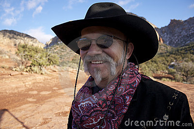 Cowboy de sourire avec des lunettes de soleil dans les roches rouges