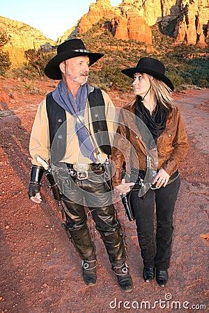 Cowboy e cowgirl que olham cada outro largo