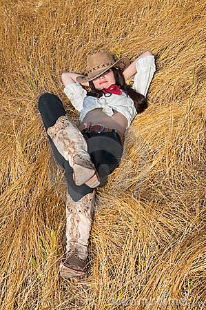 Cowboy girl lying in a field of grass