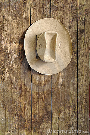 Cowboy hat hanging on an old wooden wall