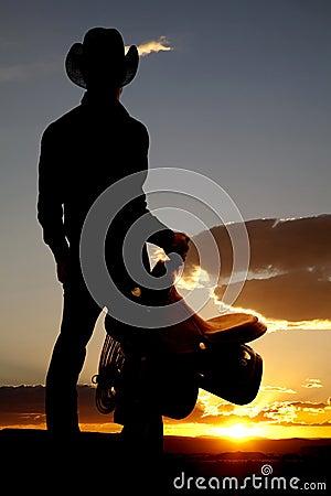Cowboy holding saddle silhouette